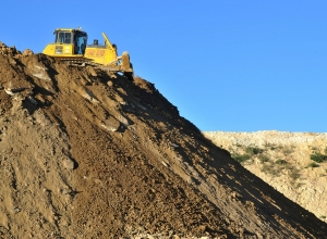 A bulldozer pushes earth in the discharging zone